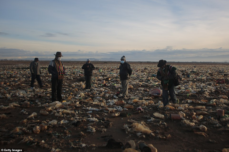Local villagers Fidel Quispe, Cesar Condo, Felix Quiros, and Roberto Tarquiwalk among the plastic waste that has built up over several years