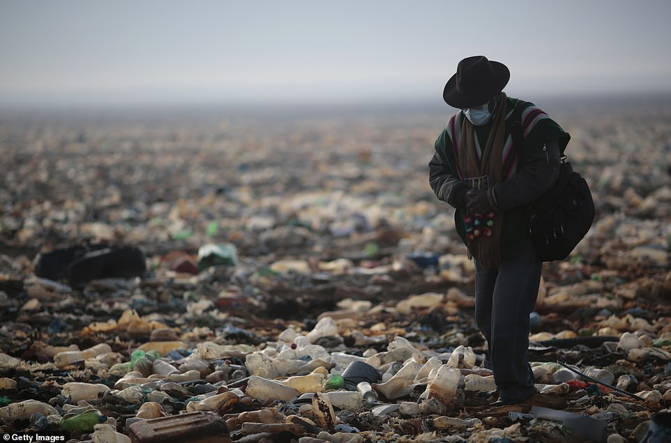 Residents of villages surrounding Lake Uru Uru must go to Oruro to buy drinking water and many are concerned for the future of their communities (pictured, villager Roberto Tarqui walks over the mountains of rubbish)
