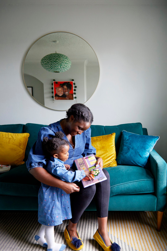 Vanessa and daughter Ariella read book together on a blue velvet sofa