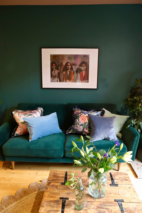 Claire Fraser Taylor living room Green velvet sofa with blue and pink cushions and artowork of three women