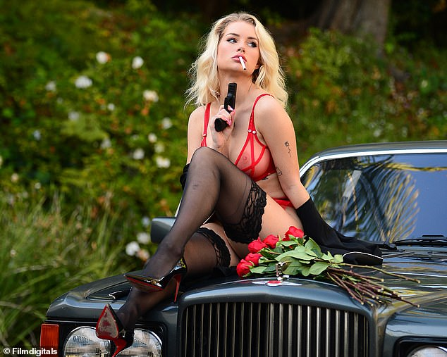 Sexy:Lottie showed off her every inch of her incredible figure in the plunging sheer red bra and matching thong bottoms as she posed on the bonnet of a vintage car