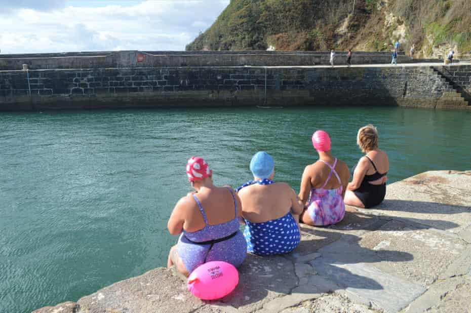 Four swimmers sit on the harbour wall overlooking the sea, near St Austell, Cornwall.