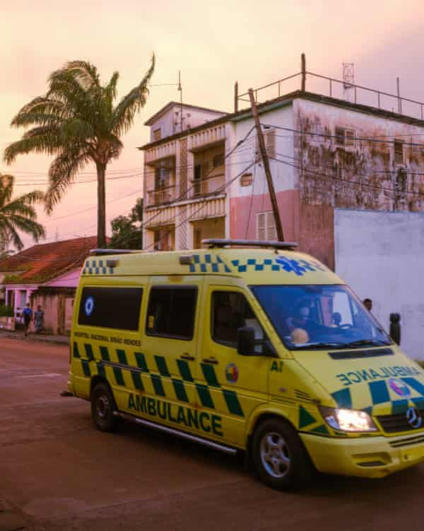 An ambulance drives passes in downtown Bissau.