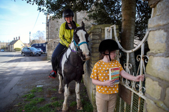 Rescue pony Micky helps owner Abi Eliot-Williams and her daughter Polly, deliver library books to members of the Hullavington Book Group