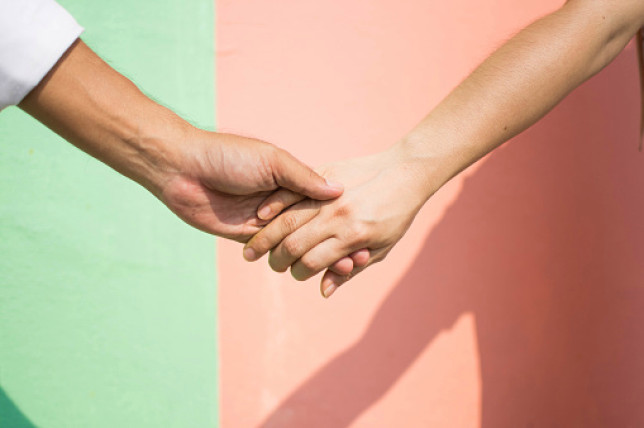Two hands holding each other against a green and pink wall
