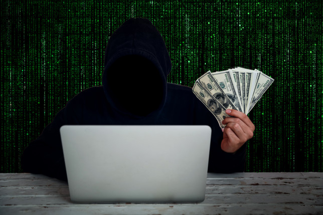 Computer Hacker Holding Us Paper Currency While Using Laptop