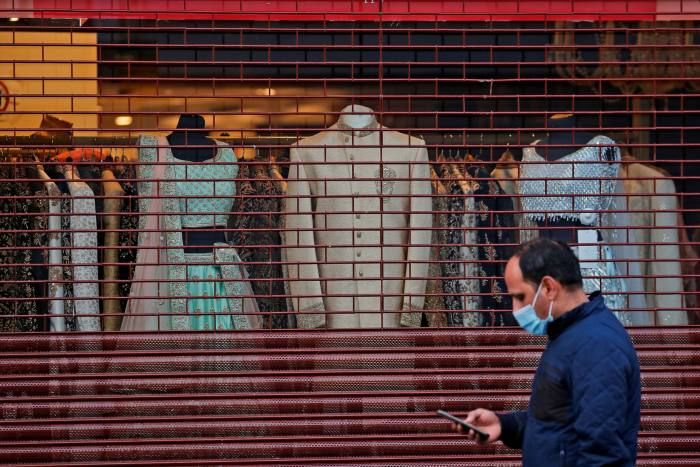 A man with a face covering walks past a closed fashion shop in London