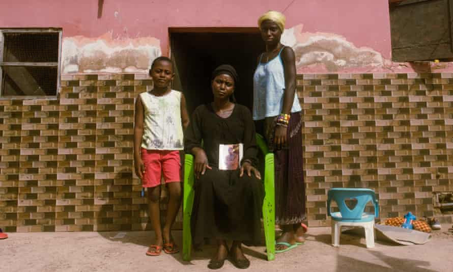 Maimuna Catchura holds the photograph of her late husband with two of couple's three children outside their home in Bissau.