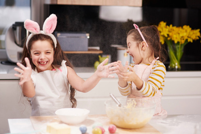 Two sisters having fun baking Easter cookies together