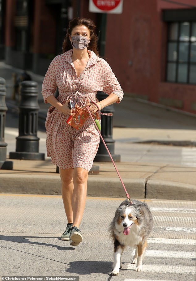 Sunny vibe: Helena Christensen, 52, looked youthful in a red-and-white patterned sundress while venturing out in New York City on Saturday with her dog Kuma for lunch on the grass
