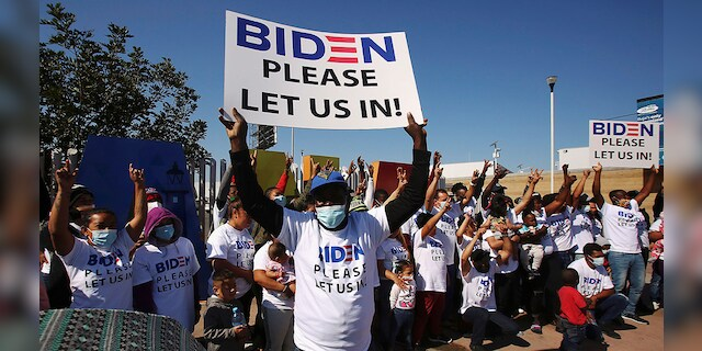 Migrants from Central America and elsewhere, hoping to cross and request asylum in the U.S., hold banners and shout slogans to President Biden. (REUTERS/Jorge Duenes)