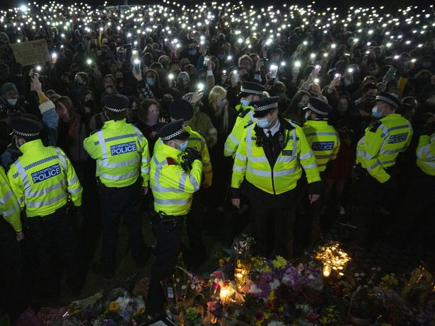 Police were seen standing on bouquets of flowers laid in memory of Sarah Everard