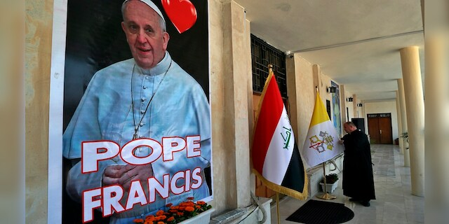 Father Nazeer Dako arranges a Vatican flag to welcome Pope Francis at St. Joseph's Chaldean Church ahead of the Pope's visit, in Baghdad, Iraq, on Tuesday. (AP)