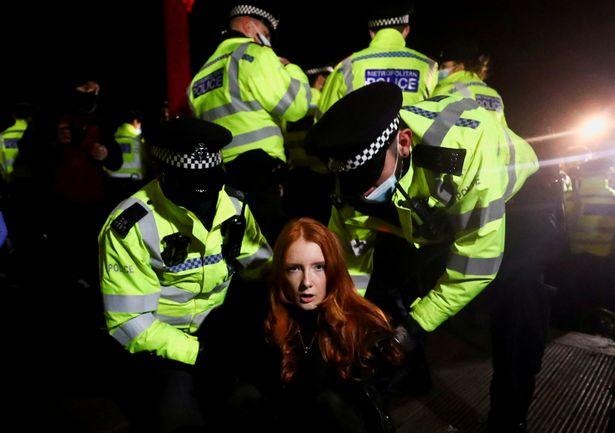 Officers were photographed kneeling on the back of a female protester