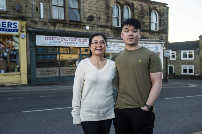 Business owner Alice Cheung, 50, outside her Chinese takeaway with son Matthew, 24, in Leeds, West Yorks. See SWNS story SWLEreviews; A straight-talking takeaway boss has gone viral for her scathing responses to bad reviews online - after telling customers not to order again if they???re not happy with their food. Alice Cheung, 50, has won admiration for her honest and hilarious rebuttals to disgruntled customers of her Oriental Express takeaway in Leeds. The Chinese takeaway has a five star review rating on JustEat, with the vast majority of customers enjoying the service from the shop. However, Alice does not hold back when it comes to responding to a minority of negative reviews. In one hilarious comeback to an angry punter, Alice urged them not to return to the takeaway and joked about looking into a 'crystal ball' to try to predict delivery times.