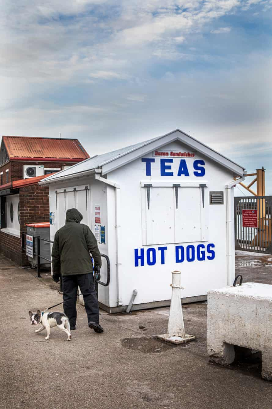 A man walks his dog past the many small food and drink outlets that have remain closed at the harbour in Whtiby.