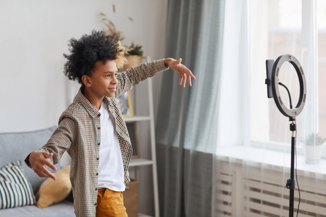Kid recording himself dancing in front of a ring light