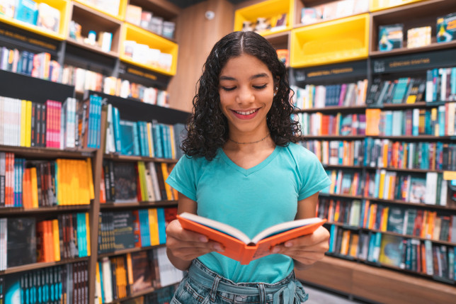 young girl reading in a bookshop
