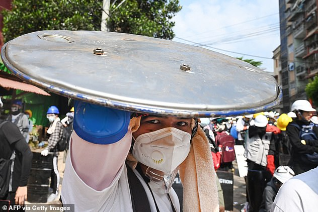 A protester holds a homemade shield during a march against the military coup in Yangon