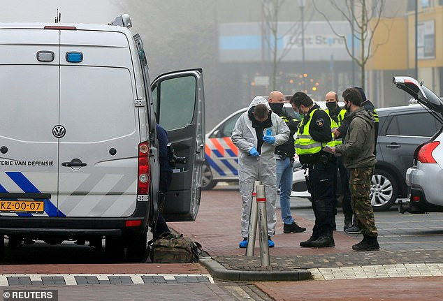 An investigator puts on a forensic suit as other emergency workers stand by a van at the scene of the explosion in Holland today