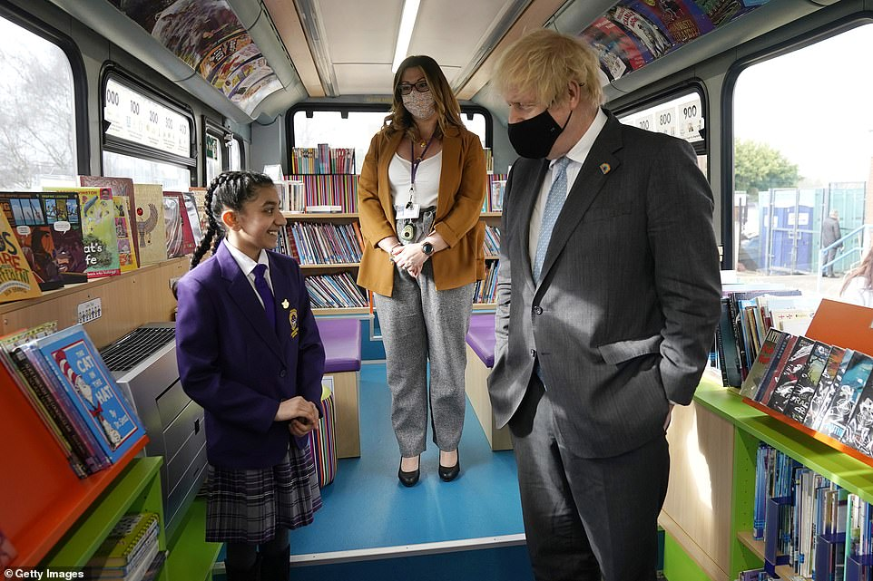 Wearing a mask, Mr Johnson chatted to head girlHirah Hussain on a bus library during a visit to St Mary's CE Primary School
