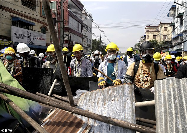 Demonstrators gather behind a barricade during a protest against the military coup in Yangon
