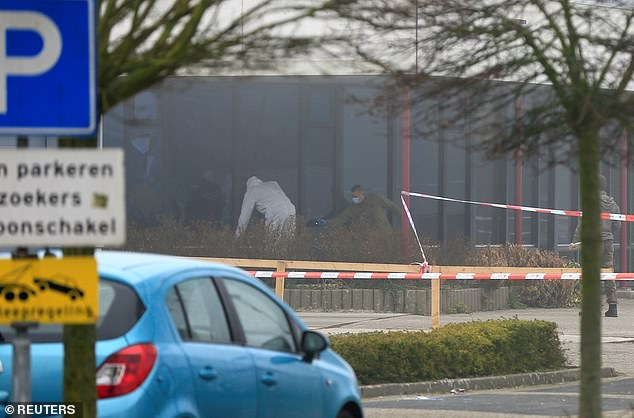 Emergency responders investigate the site of the explosion which police say appeared to have been caused deliberately