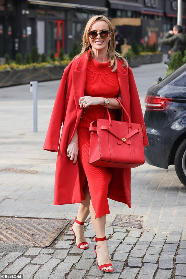 Ravishing in red:The presenter, 50, caught the eye in a bold appearance, consisting of a chic jumper dress, a matching coat and heeled sandals