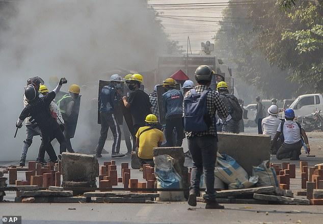 Anti-coup protestors standing behind makeshift-shields brave teargas in Mandalay, Myanmar
