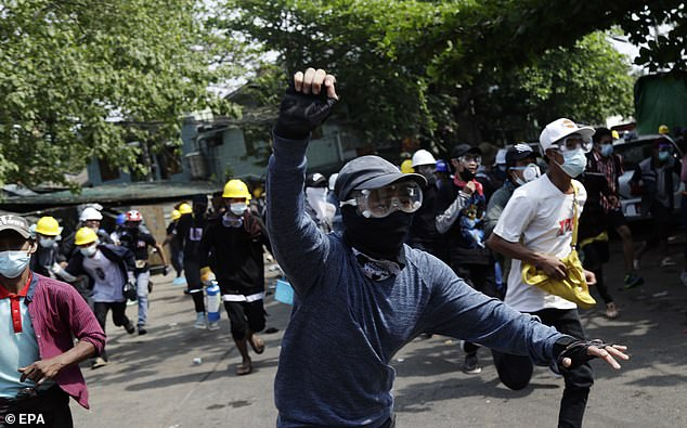Demonstrators flee as riot police officers advance on them during a protest against the military coup in Yangon
