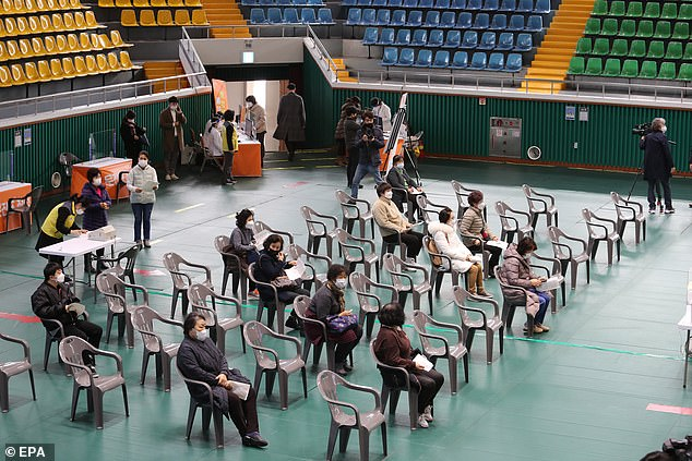 South Korea began vaccinating its population last week, and has so-far given the AstraZenca jab to 86,000 people (pictured, people wait to be vaccinated at a gym in Yeosu)