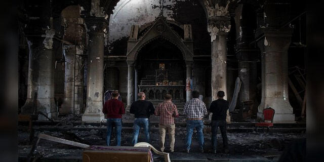 In this November 2016 photo, Iraqi Christians pray at the Church of the Immaculate Conception, damaged by Islamic State fighters during their occupation of Qaraqosh, east of Mosul, Iraq. (AP)