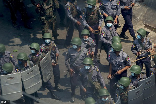 Policemen and soldiers armed with guns and slingshots advance towards anti-coup protesters in Mandalay, where two people were shot dead