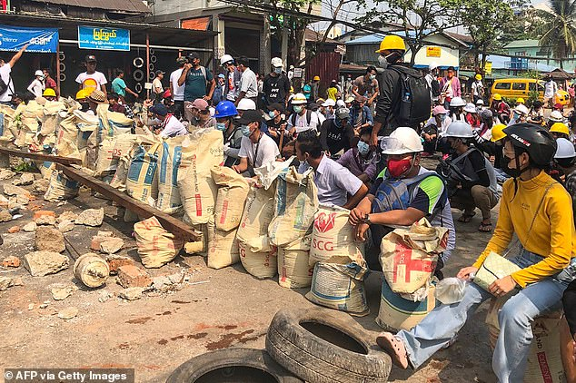 Protesters take cover behind makeshift barricades during a demonstration against the military coup in Yangon
