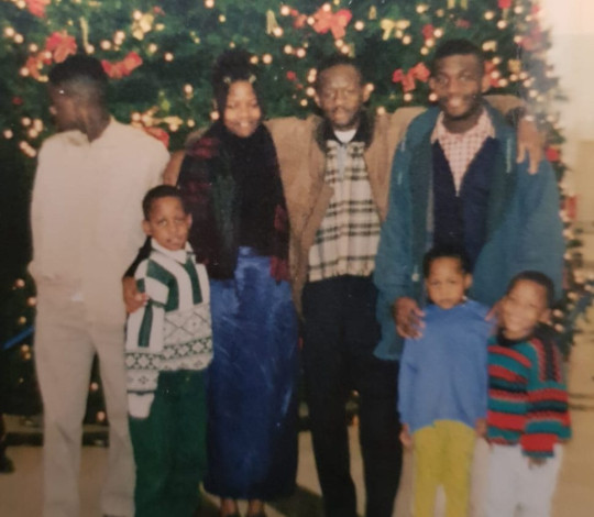 Leonard Sekyonda stands with his family infront of a christmas tree, two years before his dad's dealth