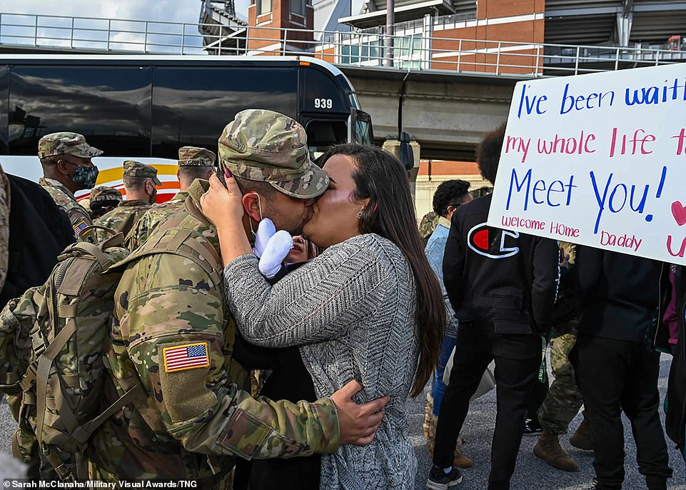 In this especially emotional photograph members of the 729th Quartermaster Composite Supply Company, Maryland National Guard, are greeted after returning from their 11-month deployment supporting NATO operations in Europe in November 17, 2020, at a parking lot across from the M&T Bank Stadium in Baltimore. One loved one even created a sign which read 'I've been waiting my whole life to meet you! Welcome home Daddy'