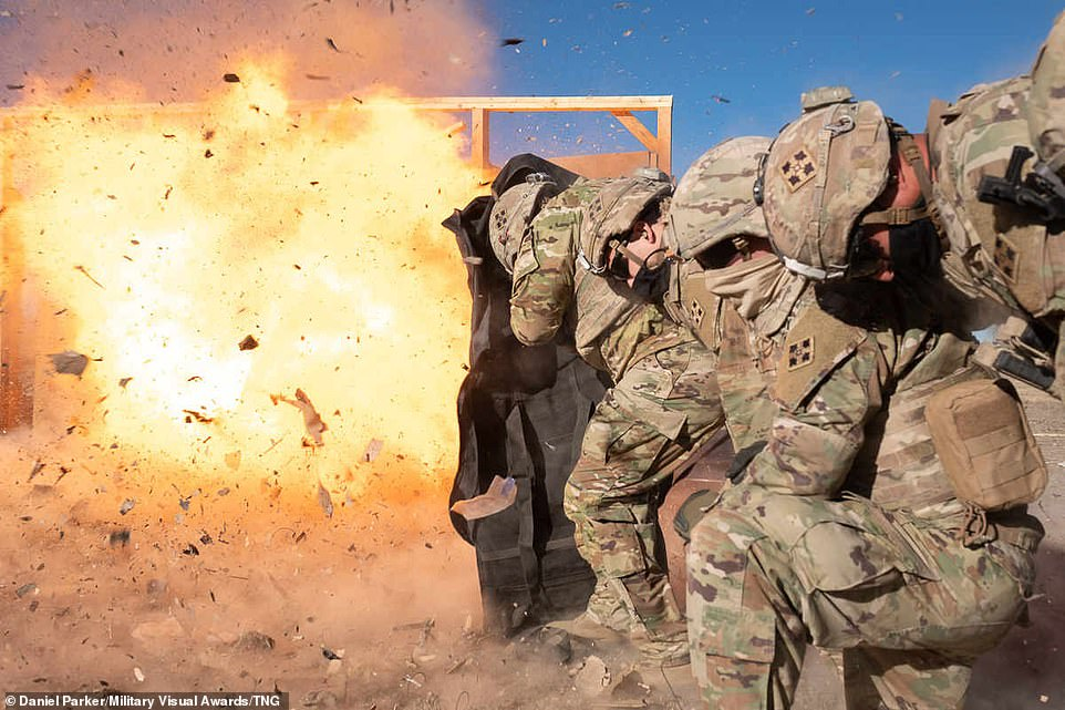 Soldiers assigned to 1st Stryker Brigade Combat Team, 4th Infantry Division, stack up against a simulated door for a silhouette charge at Fort Carson, Colorado, on December 7, 2020. The 299th BEB hosted the breach academy for non-combat engineer soldiers from across the brigade who huddled together and shielded themselves from the enormous blast