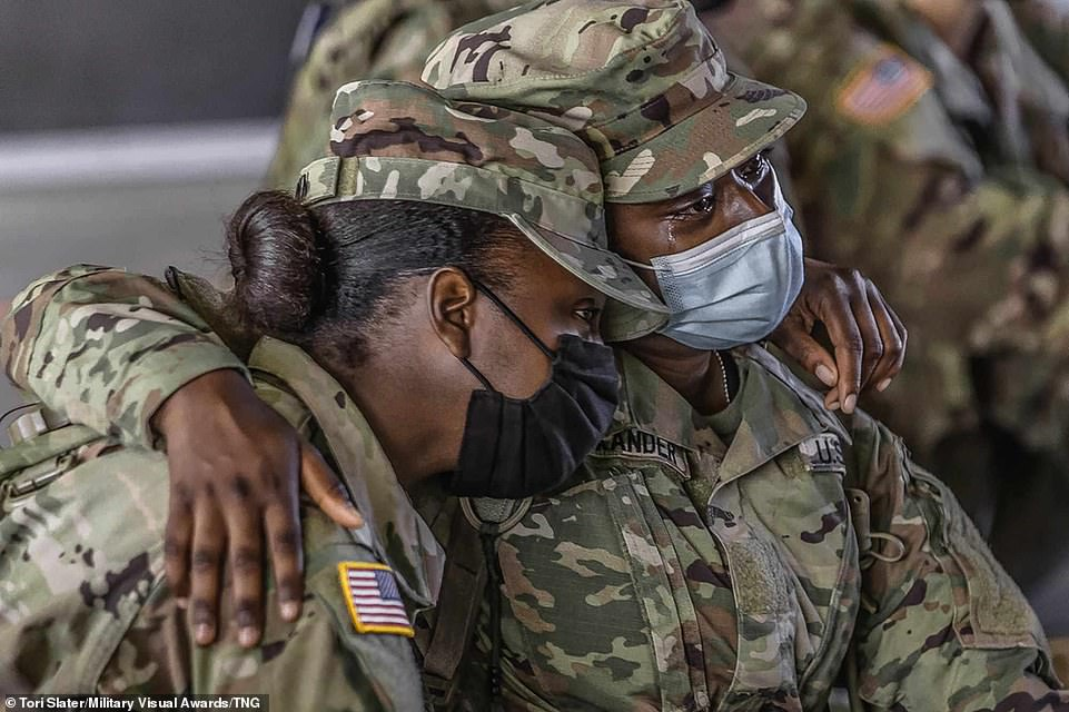 Tears flow from one soldier's eyes as they hug a colleague, both of which are wearing masks and their uniforms, while providing support for each other during the coronavirus pandemic