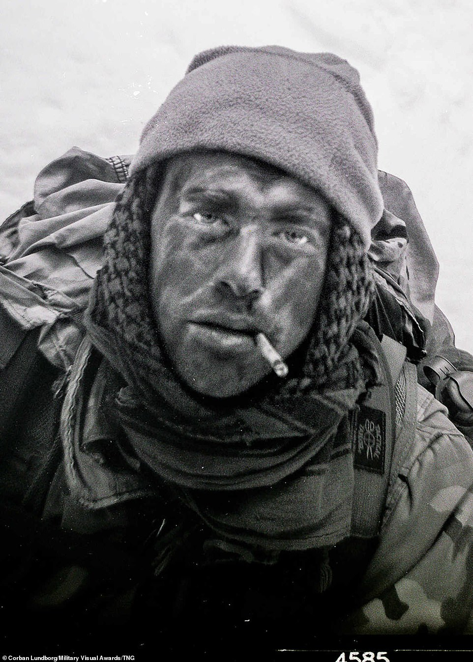 In a photograph which looks dated but was in fact taken on February 25, 2020, an Airman applies camouflage to his face while appearing to smoke during Survival, Evasion, Resistance and Escape training, at the Fairchild Air Force Base, Washington
