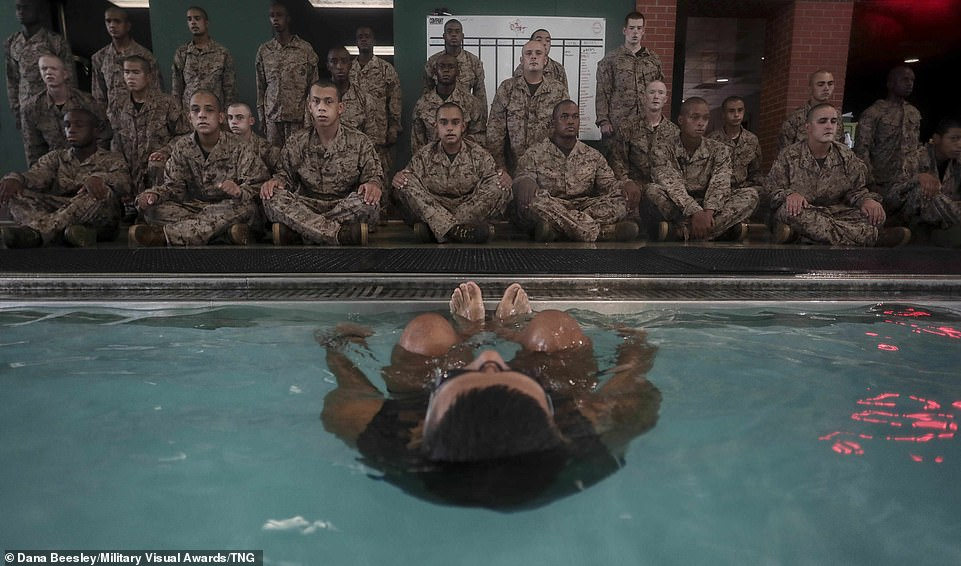 A Marine Corps Instructor of Water Survival instructs recruits who sit cross-legged paying close attention to the event which taught them proper breathing techniques before taking swim qualification training on Marine Corps Recruit Depot Parris Island, South Carolina on September 29, 2020. Swim qualification is one of the first graduation requirements recruits face in training