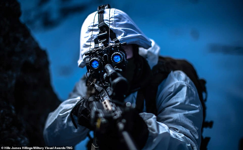In this impressive picture, a member of the Dutch infantry brigade can be seen looking the sight of their firearm during cold weather training in Austria