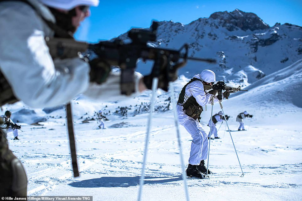 Dutch infantry brigade stand in formation pointing their weapons which have been placed on top of a white stand during cold weather training in Austria, with the backdrop of snow-covered mountains
