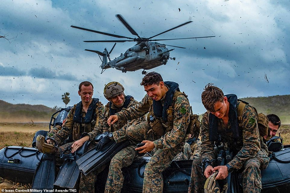 Marines with the 31st Marine Expeditionary Unit's Maritime Raid Force laugh and joke with each other while they hold down a combat rubber raiding craft as a CH-53E Super Stallion helicopter with Marine Medium Tiltrotor Squadron 265 prepares to land during Cobra Gold 20 in Hat Yao, Kingdom of Thailand