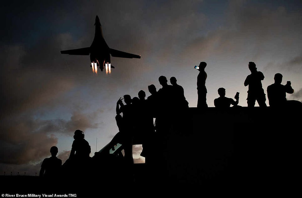 The 9th Expeditionary Bomb Squadron B-1B Lancer mechanics take selfies as a B-1B flies overhead at Andersen Air Force Base, Guam, in the western Pacific, on May 21, 2020. As the night draws in it creates an impressive silhouette of the plane which flies overhead and encourages several onlookers to take out their phones to capture the moment
