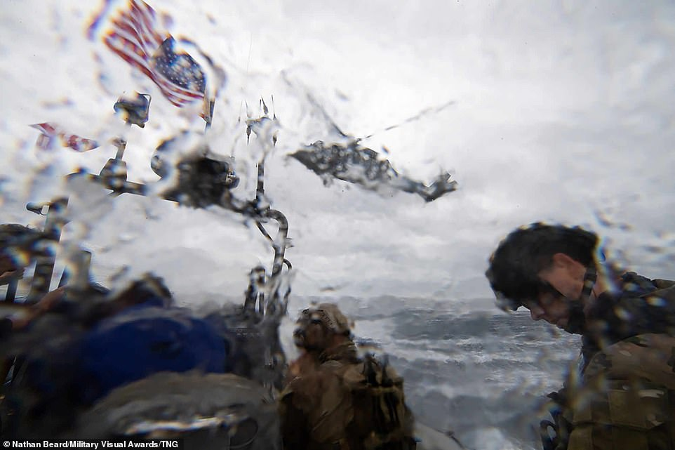 In this rain-covered image, which portrays some of the unpleasant conditions military personnel have to contend with, US Navy Sailors and US Coast Guardsmen conduct helicopter hoist training aboard a rigid hull inflatable boat on the choppy ocean waters