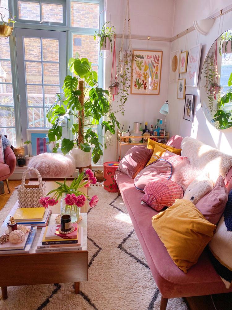 what I Rent: Zeena, one-bedroom flat in Hackney - inside Zeena's living room with pink sofa and plants