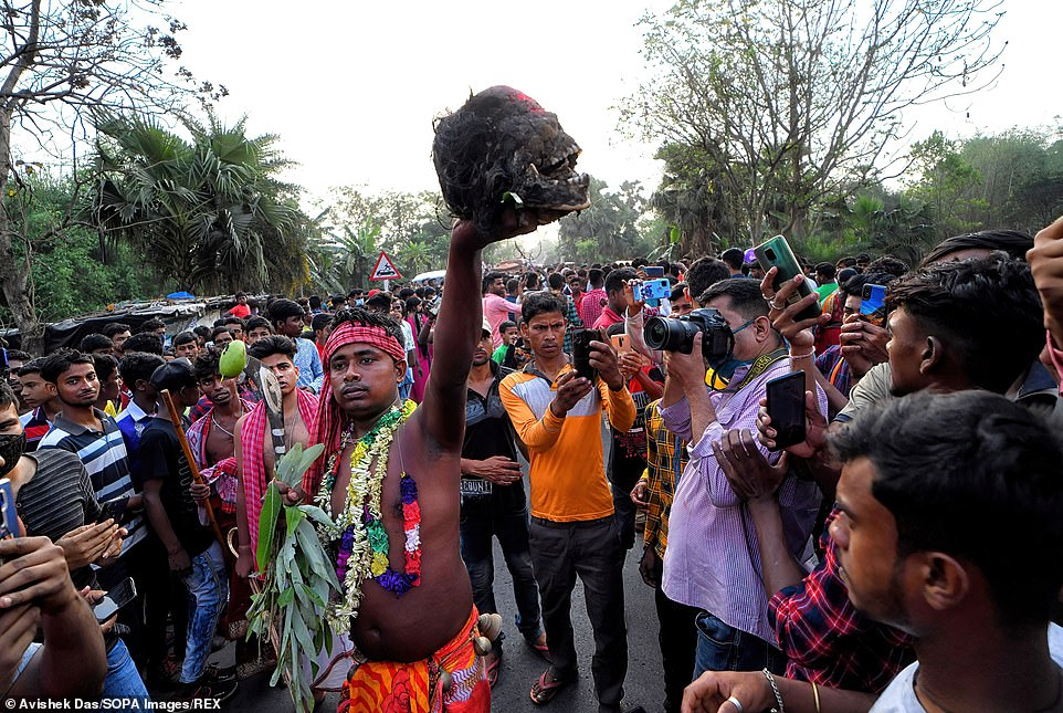 Those selected to carry the human skulls held them in their hands high above the crowds as large groups of people and took pictures of the unusual sight