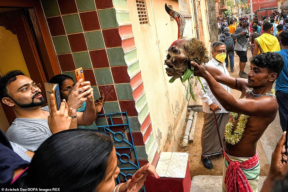 The week-long Gajan Festival is mostly celebrated in West Bengal and is associated with Hindu deities such as Shiva, Neel and Dharmaraj. Pictured: People stand on doorsteps to take pictures of the festival