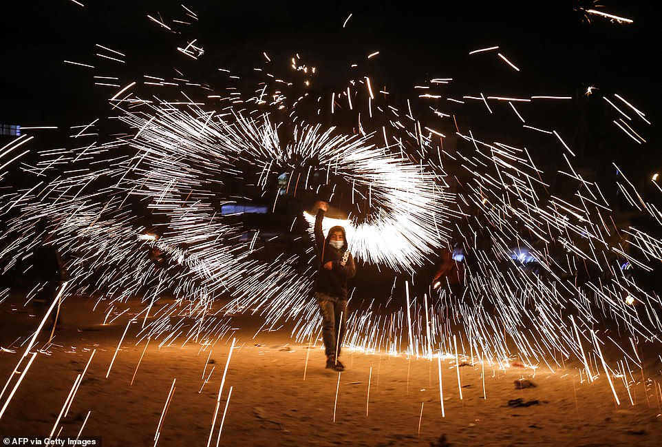 2021: A Palestinian boy waves fireworks as people celebrate the start of the Muslim holy month of Ramadan in the southern Gaza Strip town of Rafah