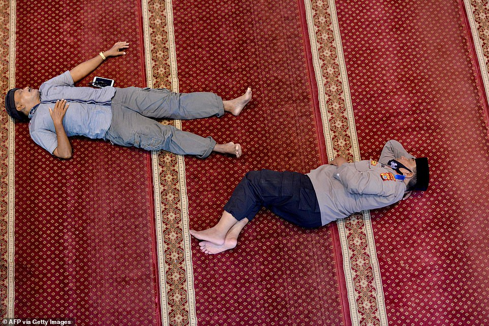 2021: Two men rest on the floor of Al Makmur mosque in Banda Aceh after prayer during the Islamic holy month of Ramadan